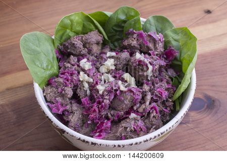 Closeup bowl of freshly cooked beef liver with red sauerkraut garlic and raw spinach leaves on rustic wood table