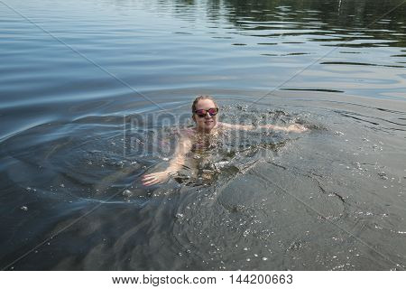 The girl swimmer floating on the river