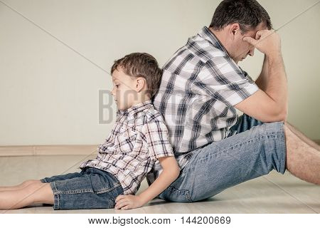 Sad son and his dad sitting on the floor at room at the day time. Concept of conflict in the family.