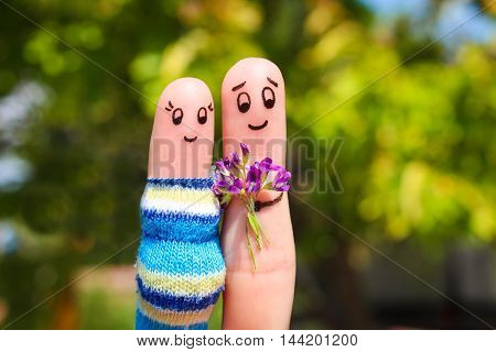 Finger art of a Happy couple. Man is giving flowers pregnant woman.