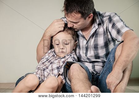 Sad son and his dad sitting on the floor at room at the day time. Concept of problem in the family.