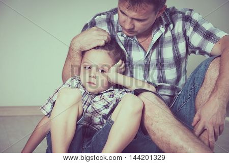 Sad son and his dad sitting on the floor at room at the day time. Concept of problems in the family.
