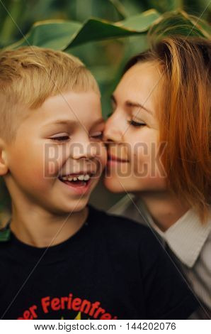 Portrait of a happy mother and her son outdoor. Series of a mother and son outdoor portrait in a park. Portrait of smiling mother and son. Family photo. The concept of a happy family.
