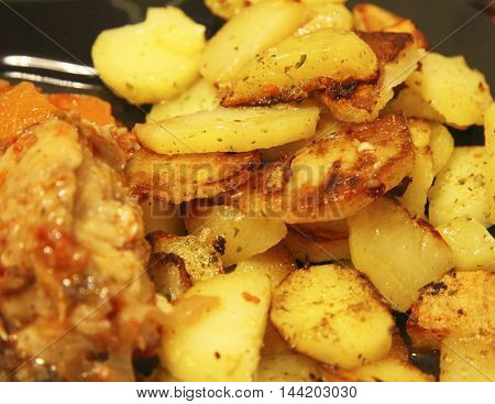 Fried potato and fried fish and the black plate