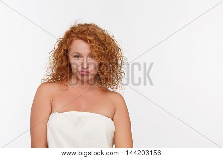 Portrait of sad mature woman with pursing lips posing in studio. Beautiful red haired senior woman looking at camera isolated on white background.