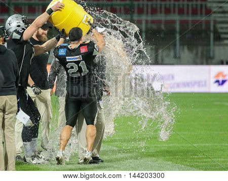 KLAGENFURT, AUSTRIA - JULY 11, 2015: Head Coach Shuan Fatah gets a Gatorade shower after a game of the Austrian Football League.