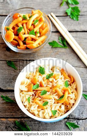 Pasta with mushrooms and fresh parsley. Vegetarian pasta in a bowl, marinated mushrooms in glass bowl, chopsticks on wooden background. Closeup