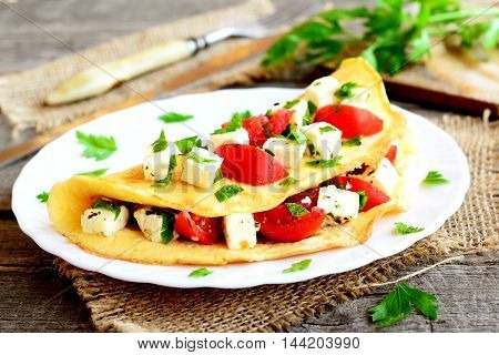 Homemade stuffed omelet on a plate. Egg omelet stuffed with fresh tomatoes, cheese and green parsley. Healthy vegetarian breakfast recipe. Fork, knife, cutting board on wooden background. Closeup