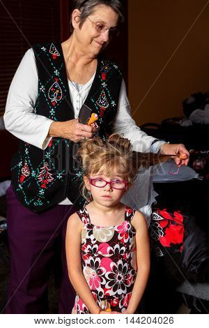 A young girl stands looking a bit sad as her grandmother removes pink foam curlers from her hair. The grandma is smiling.