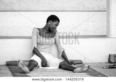 KARA, TOGO - MAR 9, 2013: Unidentified Togolese woman sits near a house. People in Togo suffer of poverty due to the unstable econimic situation