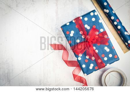 Gift box wrapped in blue dotted paper with red ribbon on a white wood old background.Wrapping materials scattered over the table.
