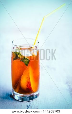 A glass with homemade ice tea peach flavored. Freshly cut peach slices for arrangement. Light blue wood background. background.