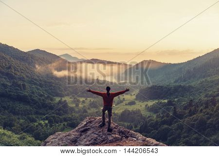 Happy young man standing with raised arms in summer mountains at sunset rear view. Toned image