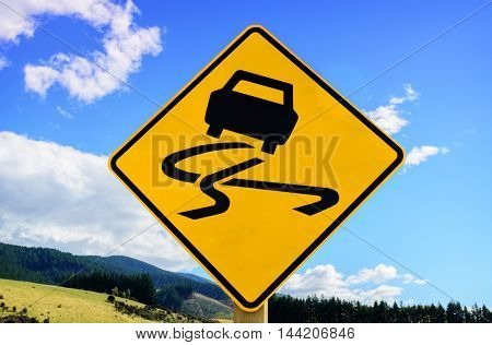 Yellow slippery road sign with blue sky background