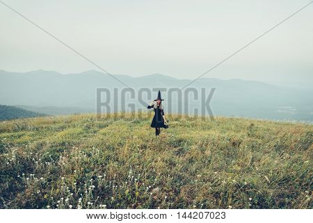 Beautiful young witch walking on autumn meadow. Theme of Halloween and magic