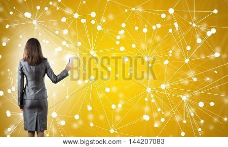 Businesswoman standing with back to camera and drawing with marker connection lines