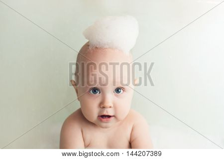 Baby bathes in a bath with soap suds on head
