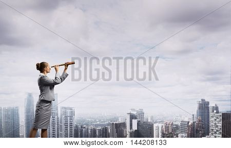 Career woman on building roof looking in spyglass over city