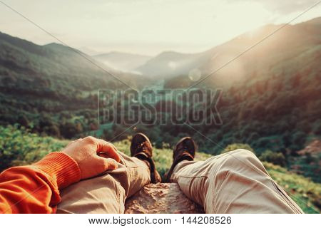 Hiker young man sitting in summer mountains at sunset point of view shot. Toned image