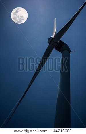 View from below of a windmill for electric power production alternative energy resources renewable energy sources. Beautiful full moon above silhouette of wind turbine outdoor at nighttime.