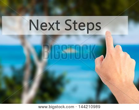 Next Steps - Hand Pressing A Button On Blurred Background Concept On Visual Screen.