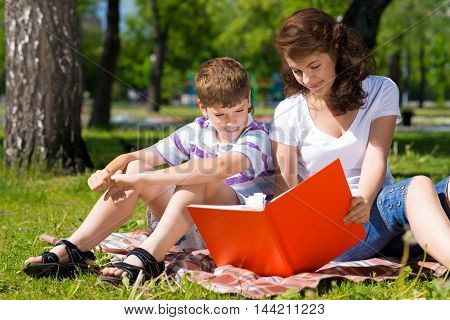 boy and a woman in a summer park reading a book together