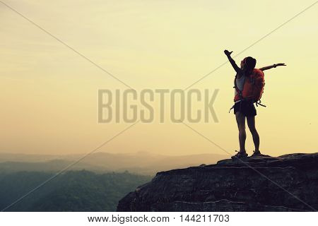silhouette of young successful woman hiker open arms on mountain peak