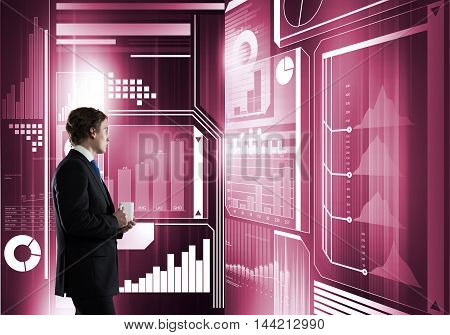 Businessman with mug in hands looking thoughtfully at media virtual screen