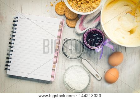 Empty recipe notebook with cheese cake ingredients prepared over a white wood background.