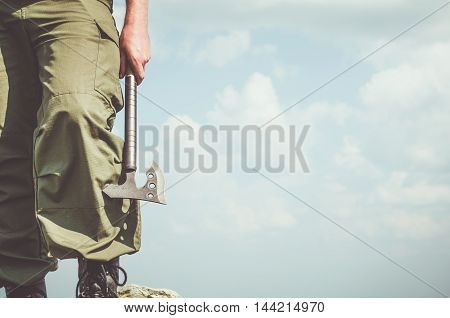 Man is holding the curved hatchet on the sky background