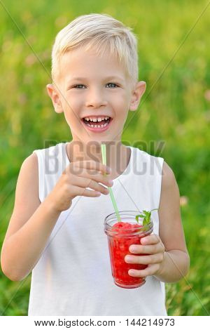Happy laughing boy holding a glass of red fresh juice watermelon. Summer time. Healthy lifestyle. Funny cute kid