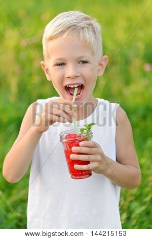 Happy laughing boy holding drinking a glass of red fresh juice watermelon. Summer time. Healthy lifestyle. Funny cute kid