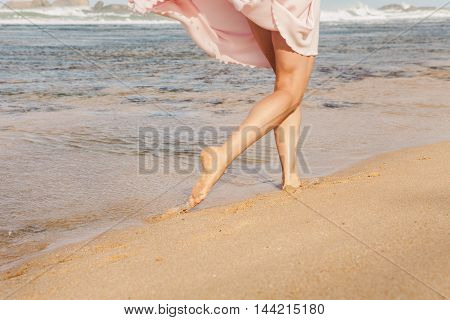 The young woman running on the beach barefoot