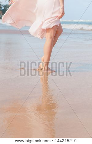 The woman legs walking on the beach sand