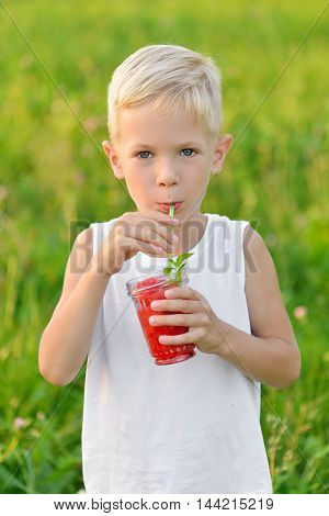 Happy laughing boy drinking a glass of red fresh juice watermelon. Summer time. Healthy lifestyle. Funny cute kid