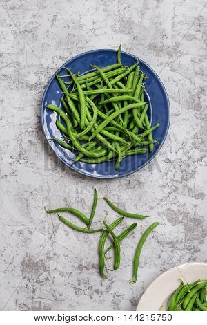 Fresh French bean in blue plate on the rough light surface top view