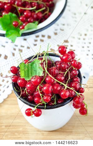 red currant berries in a vintage white mug on wooden table, selected focus