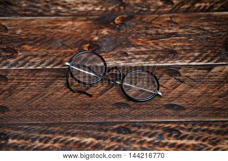 vintage round reading glasses on a wooden background