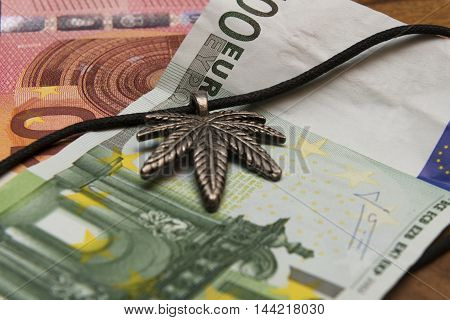Suspension leaf of marijuana and euro banknotes on a wooden table