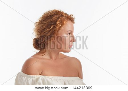 Closeup profile of middle aged woman looking away in studio. Beautiful red haired mature of senior lady looking serious isolated on white.