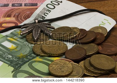 Suspension leaf of marijuana some coins euro banknotes on a wooden table