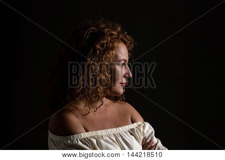 Profile of happy mature or senior woman looking away isolated on black background. Middle aged woman with red hair in studio.