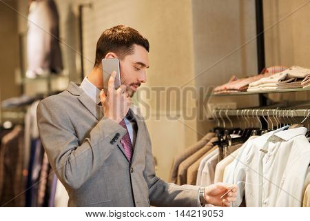 sale, shopping, fashion, communication and people concept - happy young man calling on smartphone and choosing clothes at clothing store