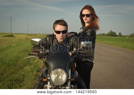 Biker Man And Girl Stands On The Road