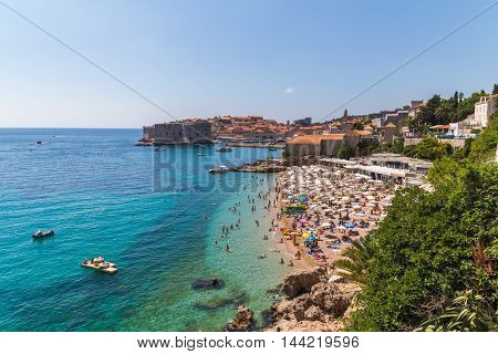 DUBROVNIK CROATIA - 10TH AUGUST 2016: A view of Banje Beach the Adriatic Sea and Old Town in Dubrovnik during the day in the summer. Large amounts of people can be seen.