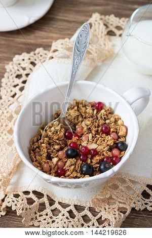 Homemade delicious healthy granola with nuts, seeds, honey and fresh berries in a ceramic cup