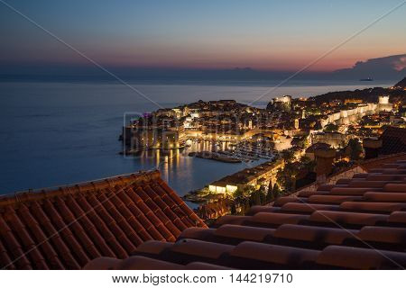 A high view of Dubrovnik Old Town at dusk showing the outside of buildings lights and the sea.