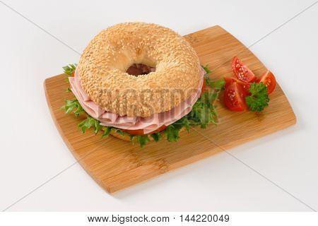 bagel sandwich with ham on wooden cutting board
