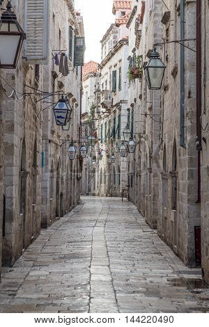 DUBROVNIK CROATIA - 11TH AUGUST 2016: A view of along quiet streets in Dubrovnik during the morning. Lamps from shops can be seen.