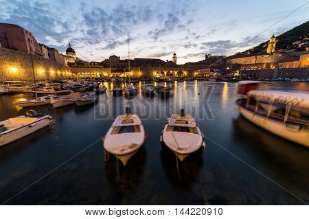 DUBROVNIK CROATIA - 11TH AUGUST 2016: Boats docked in the Dubrovnik Old Port at dusk.